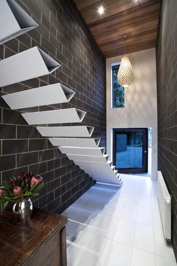 Бяло метално стълбище на тухлена стена